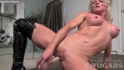Muscular cougar Mandy Foxx is masturbating in shiny thigh-high boots