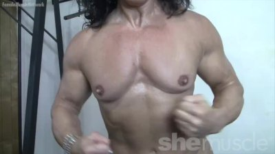 Mature female bodybuilder poses in the gym