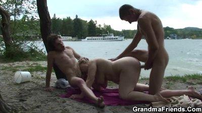 Hot grandma threesome with boys on the beach